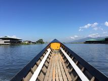 Traditional Burmese boat, sailing. Prow of a traditional Burmese boat sailing by Inle Lake, Myanmar. Paesajistica view of the lake and villages stock photos