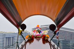 Prow tradycyjny rzecznej łodzi taxi, był decked w kwiatach, wskazuje nowożytni wysocy wzrostów budynki obok brzeg rzeki Obrazy Royalty Free