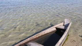 Prow of Wooden Boat on Sand near Shore. Prow of wooden boat on sandy bottom near lake shore stock footage
