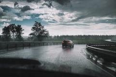 Prowadnikowy samochód w deszczu na krzywa asfaltu mokrej drodze Fotografia Royalty Free