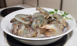 Prowns mojados crudos frescos en la placa en la estufa de cocina imagen de archivo