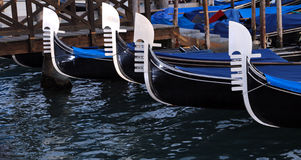 Prows of Venetian gondolas in the lagoon Stock Photography