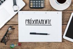 Proximamente, spanischer Text für das Kommen bald auf Notizblock im Büro Stockfoto