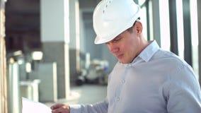 Proyecto de edificio de la ojeada del arquitecto interior de la construcción en un emplazamiento de la obra, un trabajador o un i almacen de video