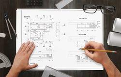 Proyecto del dibujo del arquitecto de la instalación del negocio en el escritorio del trabajo Imagen de archivo libre de regalías