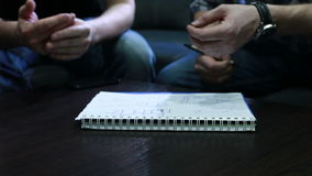 Proyecto del dibujo Manos de la gente joven que dibuja un proyecto con la pluma en el cuaderno en la oficina durante la reunión