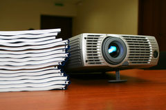 Proyector con la pila de libros Imagen de archivo libre de regalías