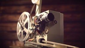 Proyector de película en un fondo negro con la iluminación dramática y el foco selectivo metrajes