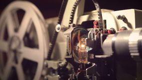 Proyector de película en un fondo negro con la iluminación dramática y el foco selectivo almacen de video
