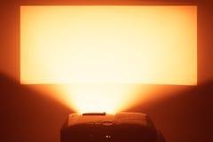 Proyector en la acción con la pantalla anaranjada caliente iluminada Fotografía de archivo