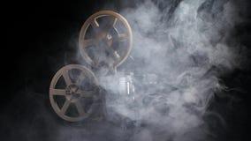 Proyector viejo que muestra la película en el humo Fondo negro del estudio metrajes