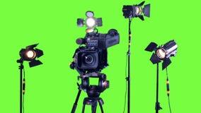 Proyectores profesionales del estudio y una cámara de vídeo profesional en una pantalla verde metrajes