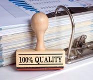 100 Prozent Qualitäts-- stempeln Sie mit Mappe im Büro Stockbilder