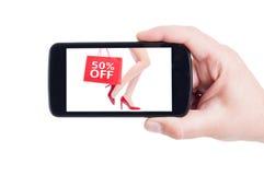 Prozentsatz fünfzig weg vom Preis für Frauenschuhe auf Smartphonekonzept Lizenzfreies Stockfoto
