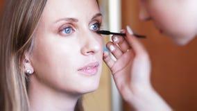 Prozess der Herstellung des Makes-up Make-upkünstler, der mit Bürste auf vorbildlichem Gesicht arbeitet stockfoto