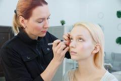 Prozess der Herstellung des Makes-up Make-upk?nstler, der mit B?rste auf vorbildlichem Gesicht arbeitet stockfotografie