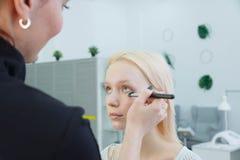 Prozess der Herstellung des Makes-up Make-upk?nstler, der mit B?rste auf vorbildlichem Gesicht arbeitet stockbilder