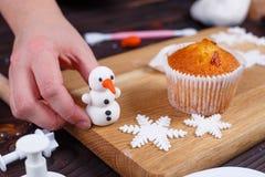 Prozess der Herstellung einer Dekoration des Schneemannkleinen kuchens von Süßigkeiten lizenzfreie stockfotos