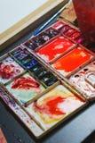 Prozess der Zeichnung mit Aquarell, ein Palettenabschluß oben Bürsten und notwendiges Zubehör Stockfotos