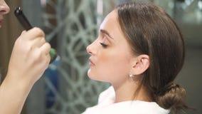 Prozess des Anwendens des Makes-up auf Gesicht junger Dame stock footage