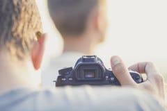 Prozess des Fotos und des Videodrehs draußen, Mann, der das Video vom Kerl ein Modell aufwerfend herstellt lizenzfreies stockfoto