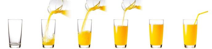 Prozess des Gießens des Orangensaftes in ein Glas stockbilder