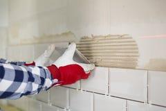 Prozess des Mit Ziegeln deckens der Fliesen in der Küche Heimwerken, bezüglich lizenzfreies stockfoto