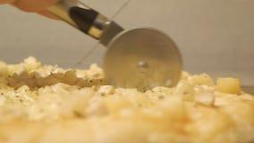 Prozess, Stadien des Kochens der Pizza saftige, appetitliche Pizza wird mit einem Metallpizzaschneider auf hölzernem Hintergrund  stock video