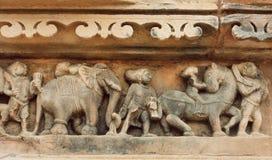 Prozession von indischen Leuten, Elefanten auf Steinwand von Khajuraho-Tempel, Indien UNESCO-Bauerbe, lizenzfreies stockbild
