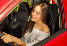 Prrety woman driving her red car while she is smiling Stock Photos
