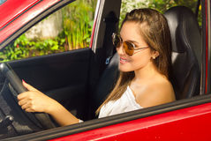 Prrety woman wearing sunglasses and driving her red car while she is smiling Stock Image
