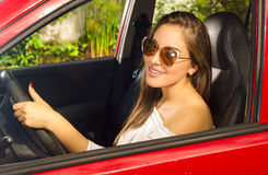 Prrety woman wearing sunglasses and driving her red car while she is smiling Stock Photo