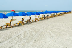 Présidences de salon de plage avec des parapluies Photographie stock