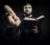 Prästen med bönen bokar Arkivfoton