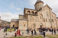 Präster och många andra personer som firar stadsdagen förbi den Svetitskhoveli domkyrkan Lokal för Unesco-världsarv Royaltyfri Bild