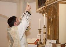 Prêtre avec l'eucharistie Photographie stock libre de droits