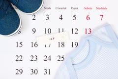 Prueba de embarazo con resultado positivo y ropa para recién nacido en el calendario, concepto de espera para el bebé imagen de archivo libre de regalías