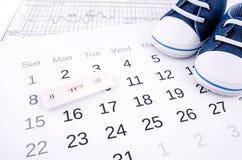 Prueba de embarazo en calendario Imagenes de archivo