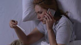 Prueba de embarazo gritadora de la tenencia de la mujer y teléfono que habla en la cama, resultado negativo almacen de video