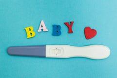 Prueba de embarazo positiva con dos tiras y la palabra 'bebé 'en un fondo azul fotos de archivo