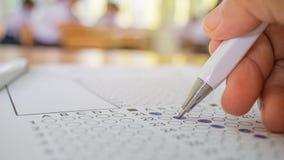 Prueba de la mano de los estudiantes que hace el examen con el selecte del dibujo de la pluma Imagen de archivo