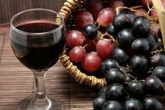 Prueba de la uva y de la botella de vino rojo Foto de archivo libre de regalías
