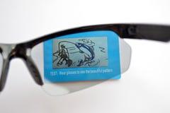 Prueba de las gafas de sol de un deporte con efecto fotocrónico sobre la imagen de prueba azul con el pescador fotografía de archivo libre de regalías