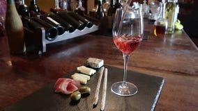 Prueba del vino, cristal, vino tinto, queso, fondo del contador de la barra Vidrios de la placa del vino y de queso almacen de metraje de vídeo