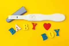 Prueba positiva para el embarazo, el corazón y la palabra 'bebé y muchacho 'en un fondo amarillo fotos de archivo libres de regalías