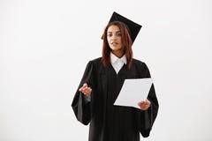 Prueba que se sostiene que escucha graduada de la muchacha africana alegre feliz sobre el fondo blanco Imagenes de archivo
