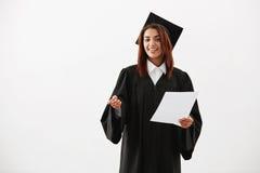 Prueba que se sostiene sonriente graduada de la muchacha africana alegre feliz sobre el fondo blanco Fotos de archivo libres de regalías