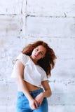 Pruebas modelo Muchacha hermosa del pelirrojo con el pelo rizado Color natural Bailando y moviendo encendido el fondo del ladrill Fotos de archivo libres de regalías