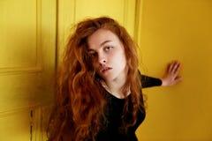 Pruebas modelo Muchacha hermosa del pelirrojo con el pelo rizado Color natural Gran contraste con las puertas de madera amarillas Foto de archivo