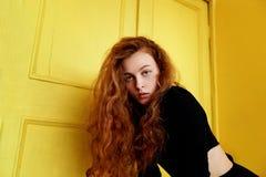 Pruebas modelo Muchacha hermosa del pelirrojo con el pelo rizado Color natural Gran contraste con las puertas de madera amarillas Imagen de archivo libre de regalías